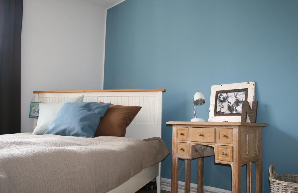 Weisses Bett vor blauer Wand