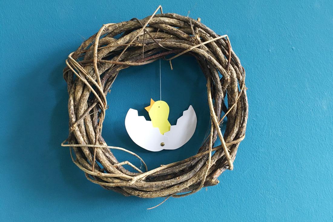 Basteln mit Kindern, Küken aus Ei geschlüpft vor blauer Wand
